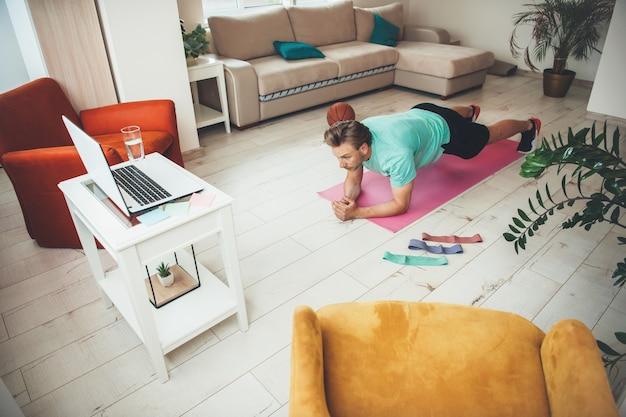 Kaukaski mężczyzna o blond włosach robi deski na podłodze, patrząc na laptopa