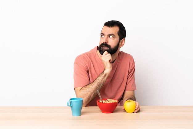 Kaukaski mężczyzna o śniadanie w stole, mając wątpliwości i myśli.