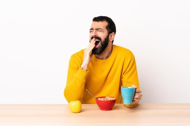 Kaukaski mężczyzna o śniadanie w stole ziewanie i obejmujące szeroko otwarte usta ręką