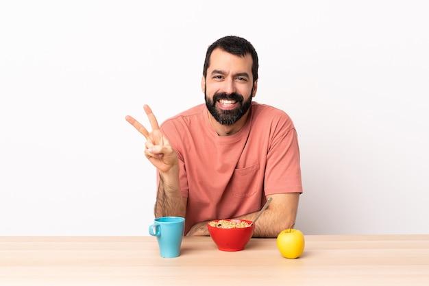 Kaukaski mężczyzna o śniadanie w tabeli uśmiechnięte i pokazujące znak zwycięstwa.