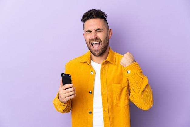 Kaukaski mężczyzna odizolowany na fioletowym tle za pomocą telefonu komórkowego i wykonujący gest zwycięstwa