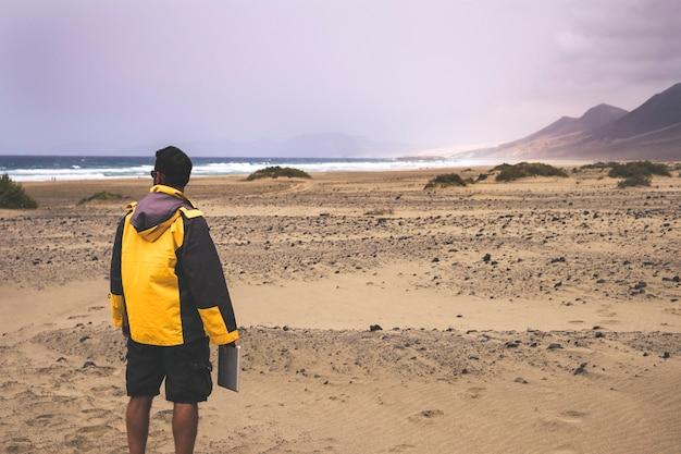 Kaukaski mężczyzna podróżnik w wanderlust cieszyć się dziką plażą z nikim tam. tablet i internet do pisania i pracy wszędzie. piękne miejsce na alternatywne wakacje. technologia i natura.