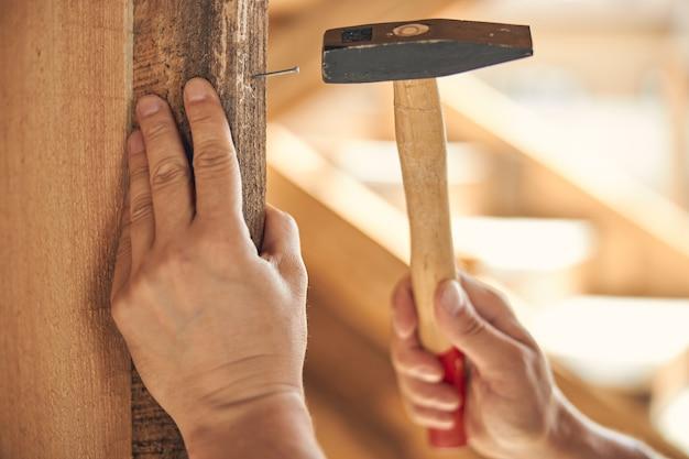 Kaukaski mężczyzna pracownik oparty jedną ręką o drewnianą belkę