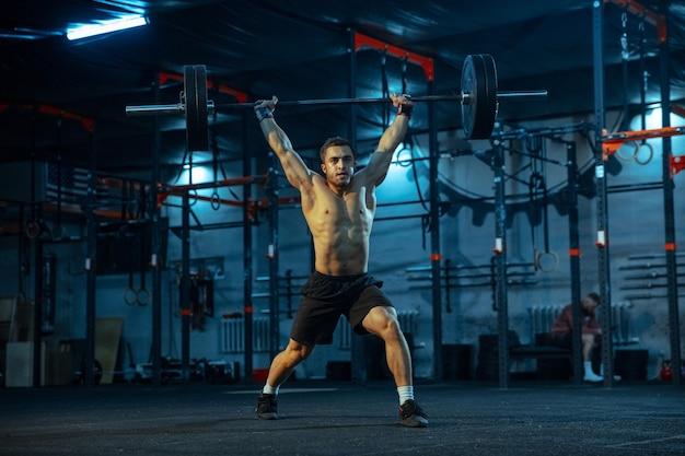 Kaukaski mężczyzna praktykujących w podnoszeniu ciężarów w siłowni. kaukaski męski model sportowy trenujący ze sztangą, wygląda pewnie i silnie. kulturystyka, zdrowy styl życia, ruch, aktywność, koncepcja działania.