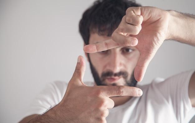 Kaukaski mężczyzna robi ramkę z rąk.