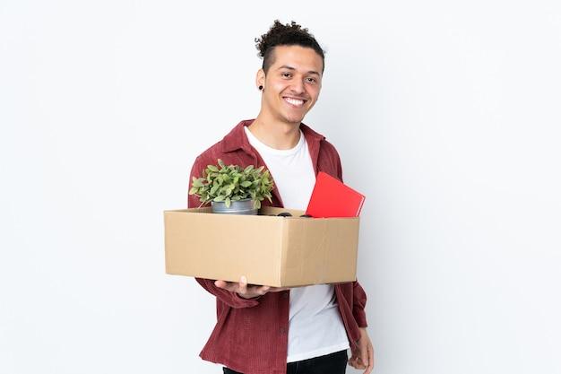 Kaukaski mężczyzna robi ruch podczas podnoszenia pudełka pełnego rzeczy na pojedyncze białe ściany z happy wypowiedzi