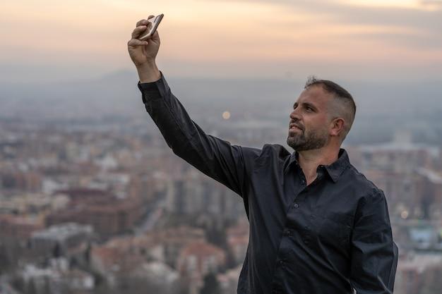 Kaukaski mężczyzna robi selfie smartfonem o zachodzie słońca