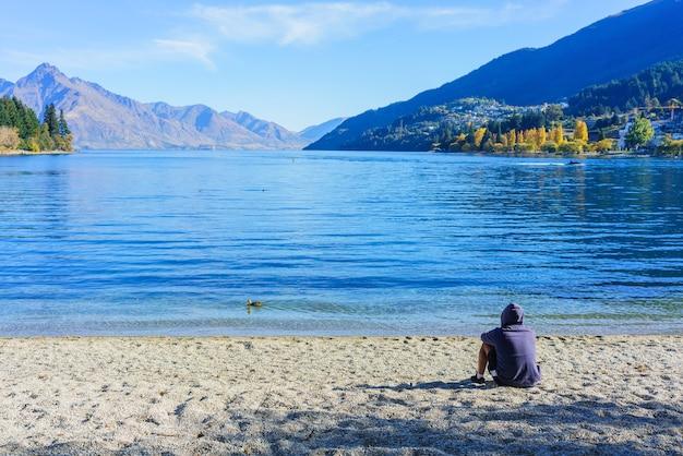 Kaukaski mężczyzna siedzący i relaksujący się na plaży jeziora wakatipu, obserwując piękno przyrody jesienią, queenstown, południowa wyspa nowej zelandii