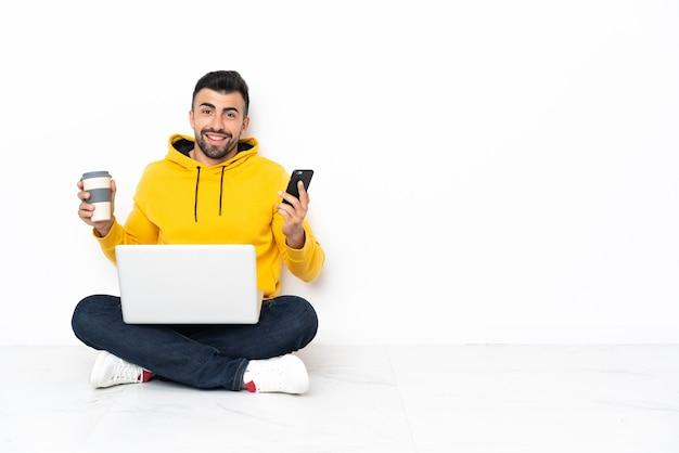 Kaukaski mężczyzna siedzi na podłodze ze swoim laptopem, trzymając kawę na wynos i telefon komórkowy