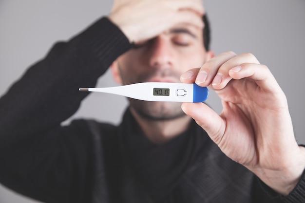 Kaukaski mężczyzna sprawdza temperaturę ciała