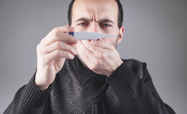 Kaukaski mężczyzna sprawdzanie temperatury w domu.