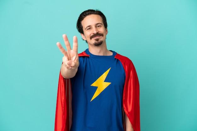 Kaukaski mężczyzna super hero na białym tle na niebieskim tle szczęśliwy i liczący trzy palcami