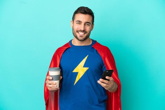 Kaukaski mężczyzna super hero na białym tle na niebieskim tle trzymający kawę na wynos i telefon komórkowy