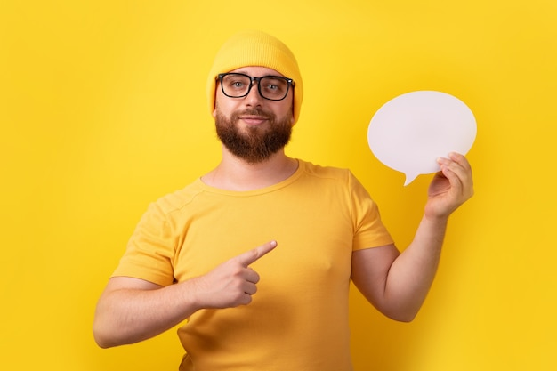 Kaukaski mężczyzna trzyma dymek z pustą przestrzenią na tekst na żółtym tle