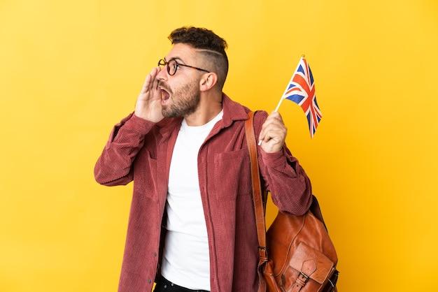 Kaukaski mężczyzna trzyma flagę wielkiej brytanii na białym tle na żółtym tle krzycząc z szeroko otwartymi ustami