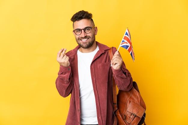 Kaukaski mężczyzna trzyma flagę wielkiej brytanii na białym tle na żółtym tle robienia pieniędzy gest