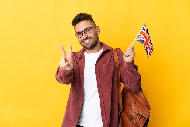 Kaukaski mężczyzna trzyma flagę wielkiej brytanii na żółtym tle, uśmiechając się i pokazując znak zwycięstwa