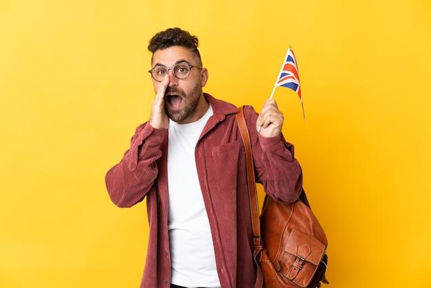 Kaukaski mężczyzna trzyma flagę zjednoczonego królestwa na białym tle na żółtej ścianie krzycząc z szeroko otwartymi ustami