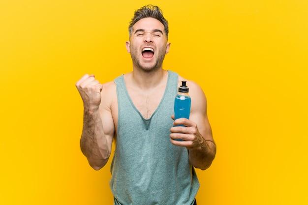 Kaukaski mężczyzna trzyma napój energetyczny doping beztroski i podekscytowany. koncepcja zwycięstwa.