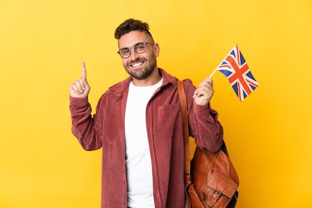 Kaukaski mężczyzna trzymający flagę wielkiej brytanii na białym tle na żółtym tle wskazujący świetny pomysł