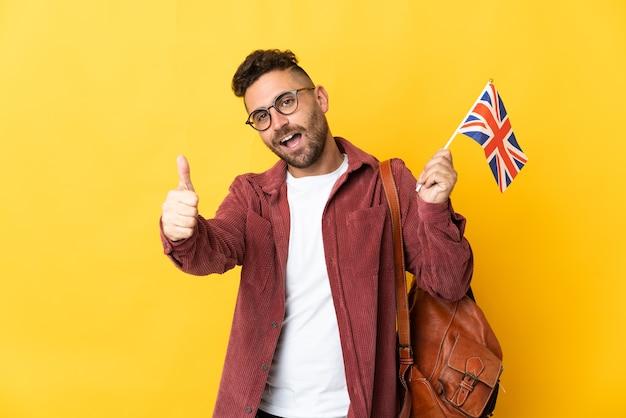 Kaukaski mężczyzna trzymający flagę wielkiej brytanii na białym tle na żółtym tle z kciukami do góry, ponieważ stało się coś dobrego