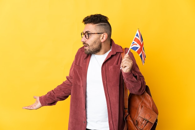 Kaukaski mężczyzna trzymający flagę wielkiej brytanii na białym tle na żółtym tle z wyrazem zaskoczenia, patrząc z boku