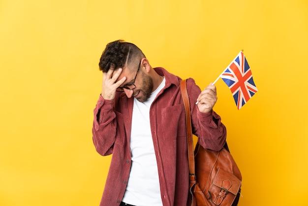 Kaukaski mężczyzna trzymający flagę wielkiej brytanii na żółtym tle ze śmiechem