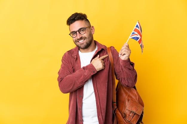 Kaukaski mężczyzna trzymający flagę wielkiej brytanii odizolowaną na żółtym tle skierowaną w bok, aby zaprezentować produkt