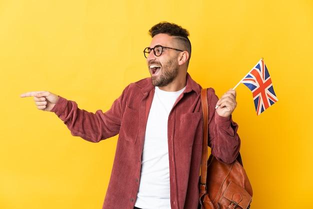 Kaukaski mężczyzna trzymający flagę wielkiej brytanii odizolowaną na żółtym tle wskazujący palec w bok i prezentujący produkt
