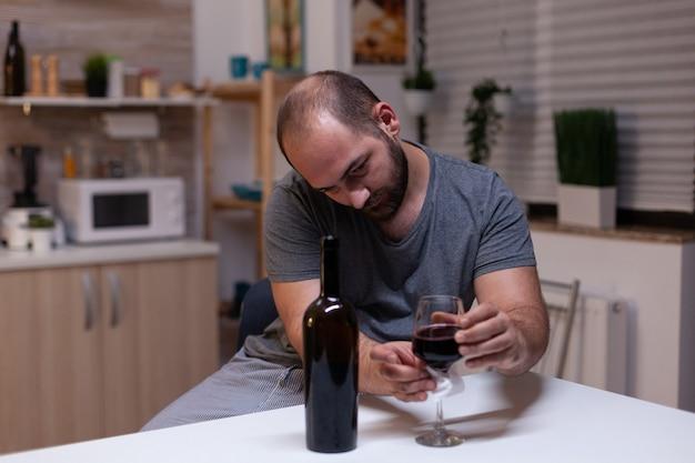 Kaukaski mężczyzna trzymający kieliszek wina siedzący w kuchni