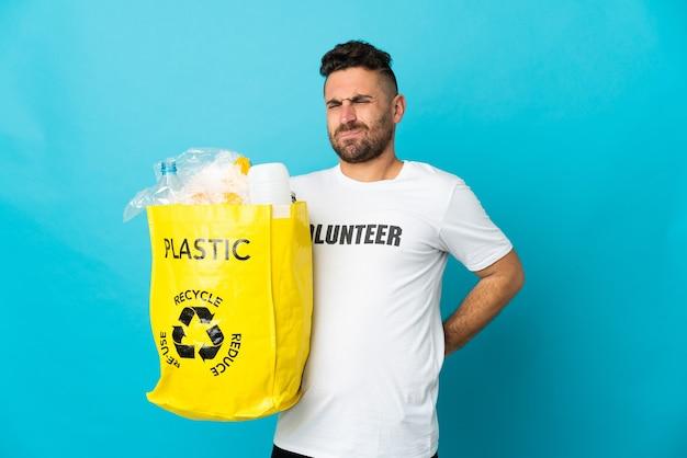 Kaukaski mężczyzna trzymający torbę pełną plastikowych butelek do recyklingu na białym tle na niebiesko cierpi na bóle pleców za wysiłek
