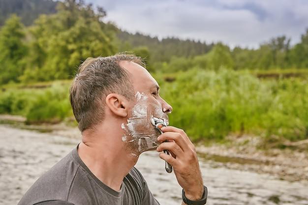 Kaukaski mężczyzna używa pianki i brzytwy do golenia twarzy podczas swojego święta w lesie.