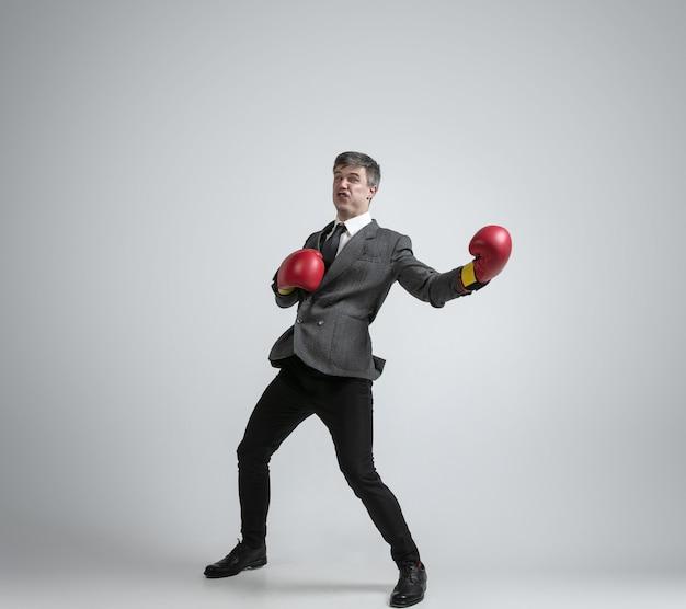 Kaukaski mężczyzna w biurze ubrania boks na białym tle na szarej ścianie