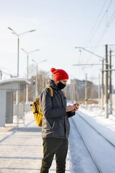 Kaukaski mężczyzna w ciemnej kurtce i czerwonym kapeluszu na dworcu czeka na pociąg i wysyła sms-y