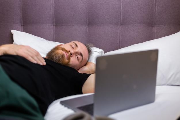 Kaukaski mężczyzna w domu na łóżku oglądając laptopa