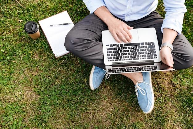 Kaukaski mężczyzna w formalnej odzieży biznesowej, siedząc na trawie w parku podczas pracy na srebrnym laptopie