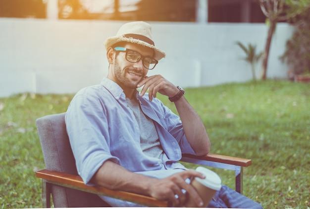Kaukaski mężczyzna w kapeluszu i okularach siedzi na krześle na zewnątrz, szczęśliwy i uśmiechnięty, relaksujący czas