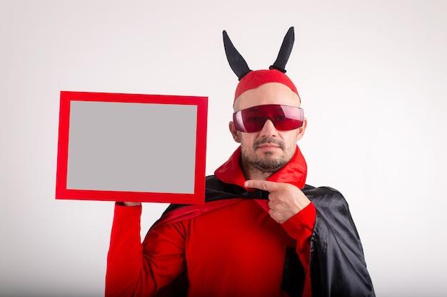Kaukaski mężczyzna w kostium na halloween, wykazując pustą tabliczkę znamionową na tle białego studia.
