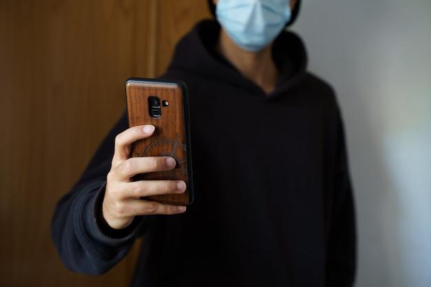 Kaukaski mężczyzna w masce chirurgicznej robi selfie smartfonem. palma de mallorca, hiszpania