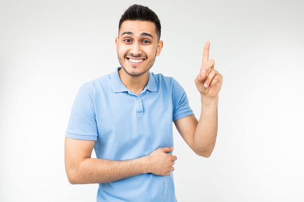 Kaukaski mężczyzna w niebieskiej koszulce oferuje pomysł pokazujący kciuk na białym
