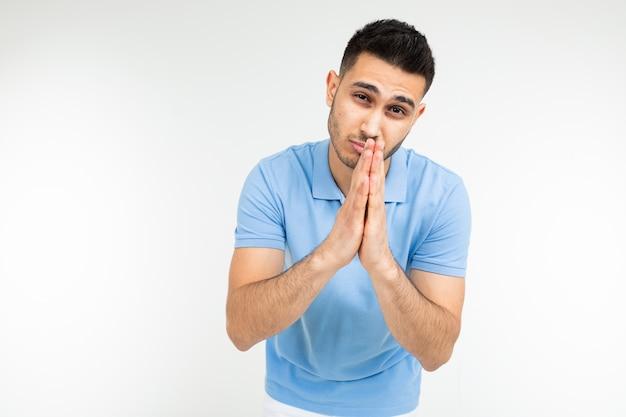 Kaukaski mężczyzna w niebieskiej koszulce szczerze prosi o coś na białym tle