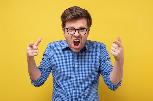 Kaukaski mężczyzna w okularach krzyczy i krzyczy. negatywna ludzka emocja twarzy