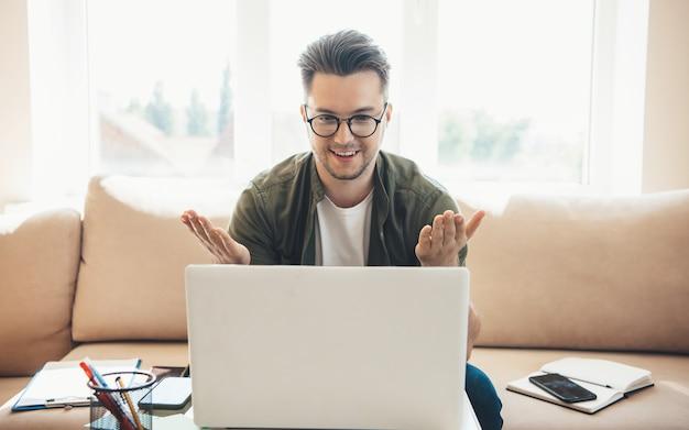 Kaukaski mężczyzna w okularach ma lekcję online w domu przy użyciu laptopa i wyjaśniając coś