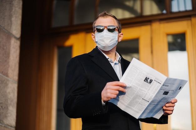 Kaukaski mężczyzna w okularach przeciwsłonecznych, masce medycznej i oficjalnym czarnym garniturze, stoi w pobliżu budynku na zewnątrz, trzyma gazetę w rękach