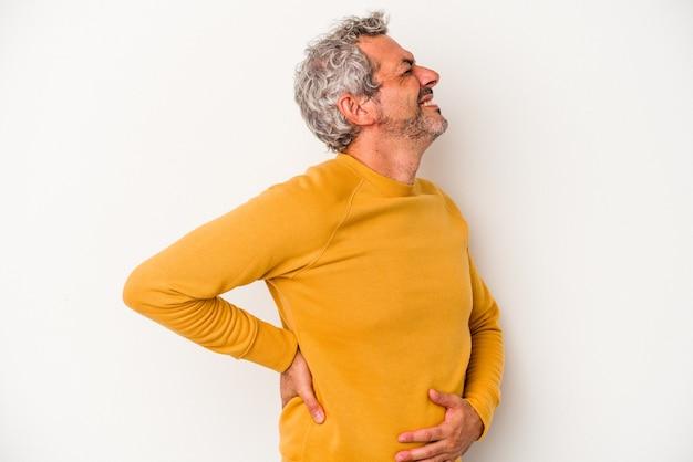 Kaukaski mężczyzna w średnim wieku na białym tle cierpi na ból pleców.
