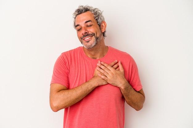 Kaukaski mężczyzna w średnim wieku na białym tle ma przyjazny wyraz twarzy, przyciskając dłoń do klatki piersiowej. koncepcja miłości.