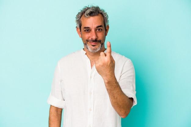Kaukaski mężczyzna w średnim wieku na białym tle na niebieskim tle wskazując palcem na ciebie, jakby zapraszając się bliżej.