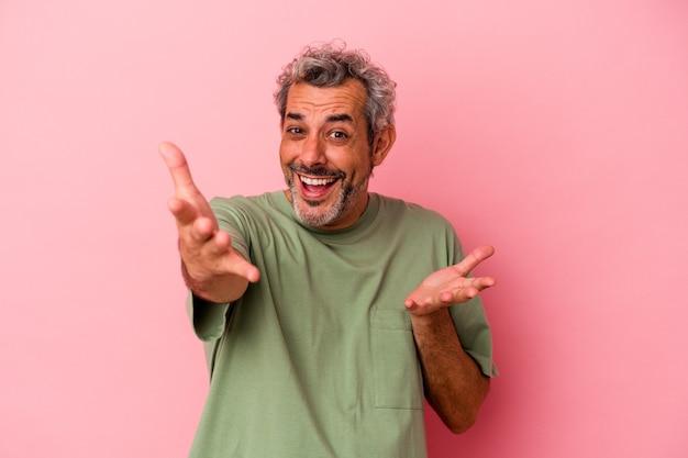 Kaukaski mężczyzna w średnim wieku na białym tle na różowym tle czuje się pewnie, przytulając się do aparatu.