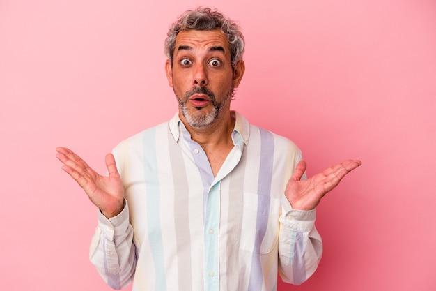 Kaukaski mężczyzna w średnim wieku na białym tle na różowym tle zaskoczony i zszokowany.