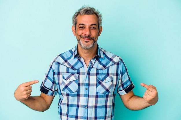 Kaukaski mężczyzna w średnim wieku na niebieskim tle osoba wskazująca ręcznie na miejsce na koszulkę, dumna i pewna siebie